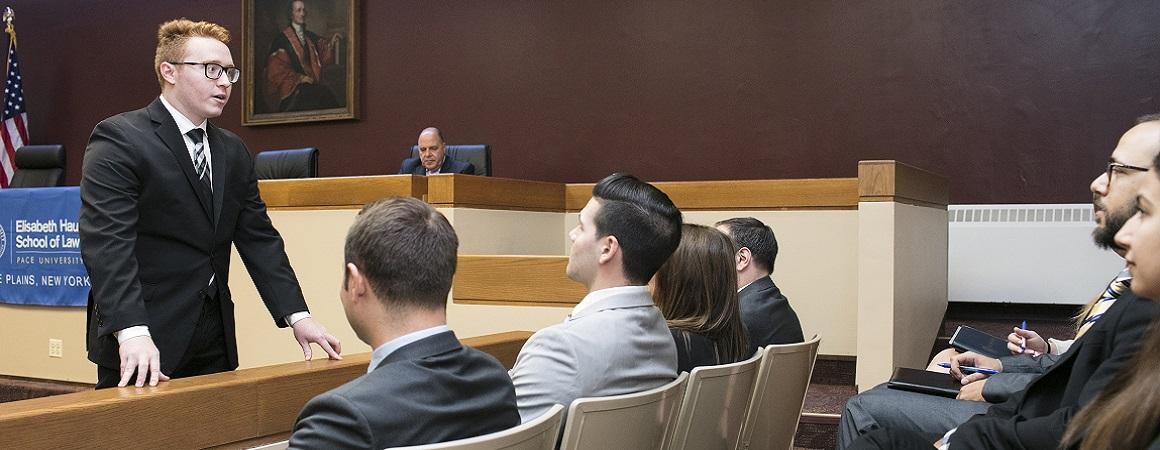 Student participating in a simulation class learning how to speak with a jury